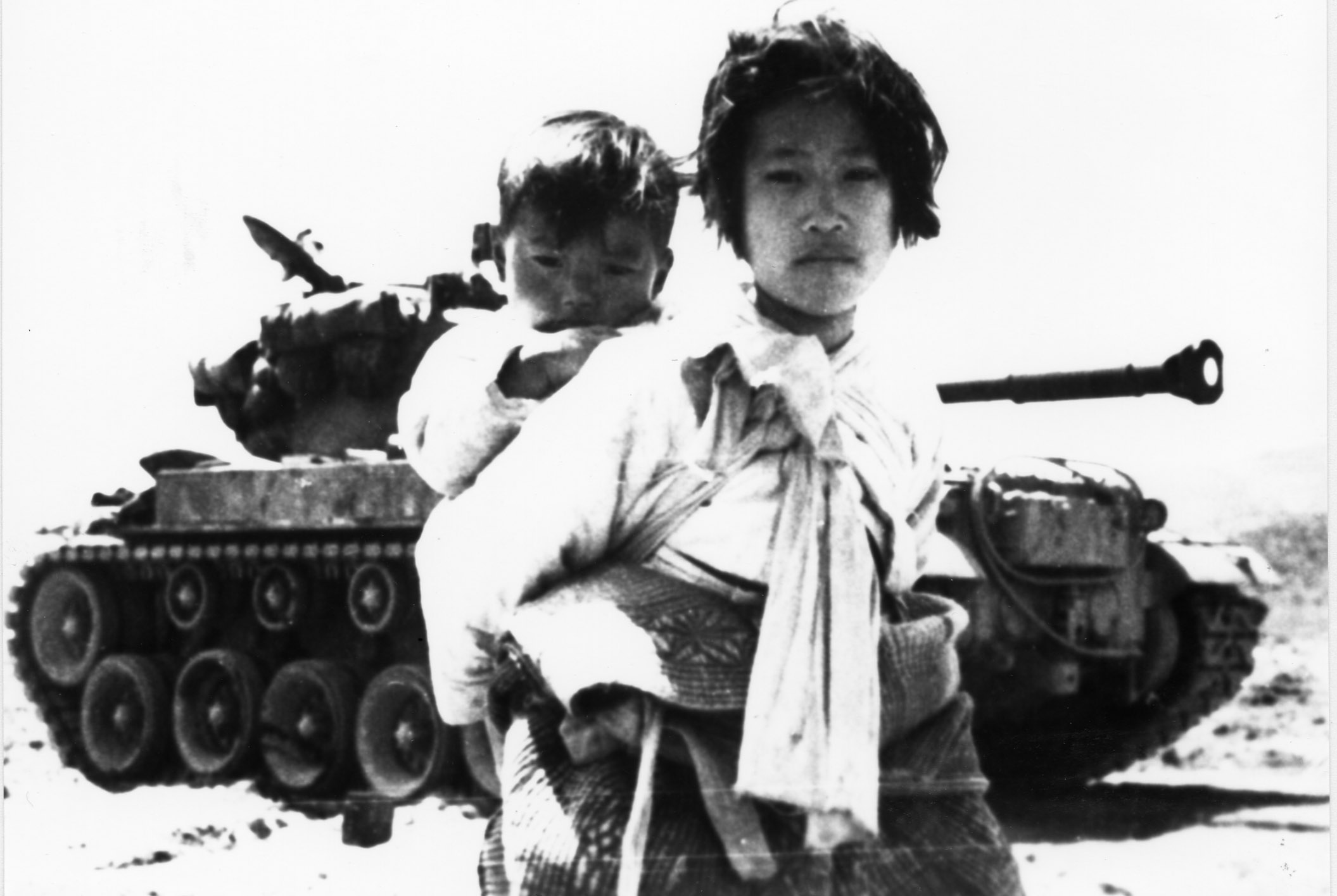 With her brother on her back, a Korean girl trudges by a stalled tank in Haengju, Korea, June 9, 1951. Photo by Air Force Major R. V. Spencer