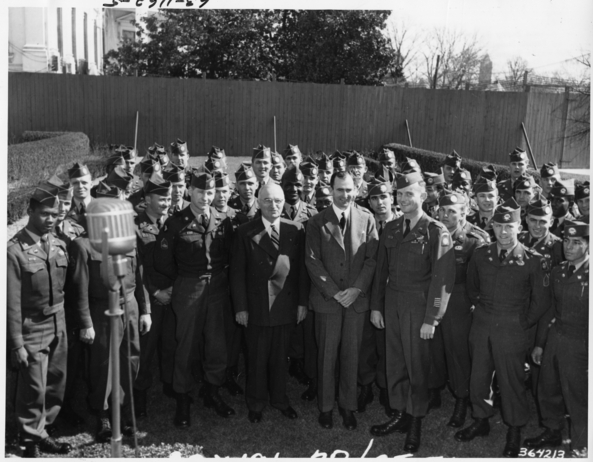 President Harry S. Truman (front row, fifth from right) and Secretary of the Army Frank Pace (front row, fourth from right) with members of the integrated 82nd Airborne in the Rose Garden behind the White House. All others are unidentified. (Truman Presidential Library, 63-1162-05)