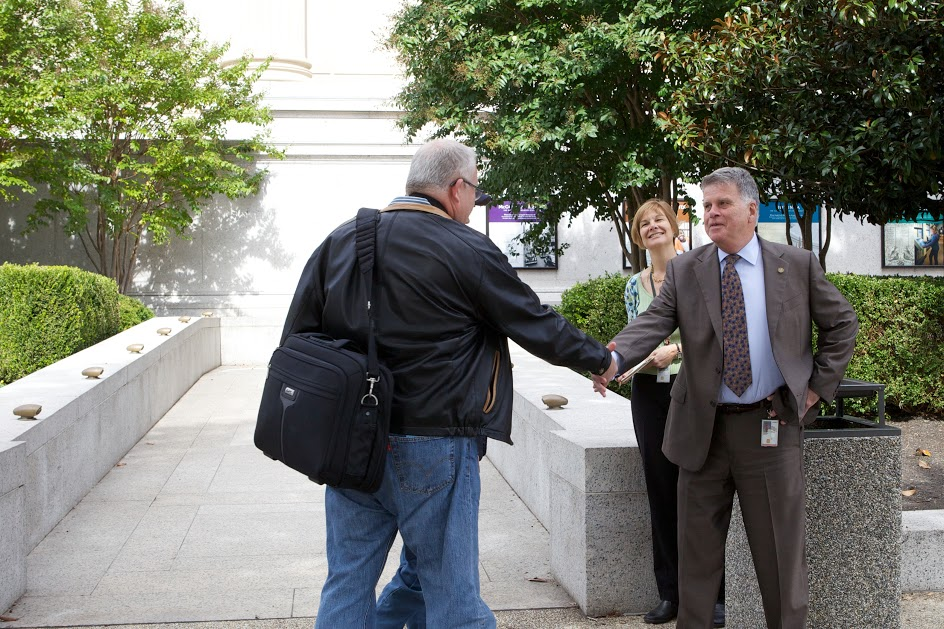 Archivist of the United States David Ferriero welcomes a visitor to the reopened National Archives Museum on October 17, 2013.