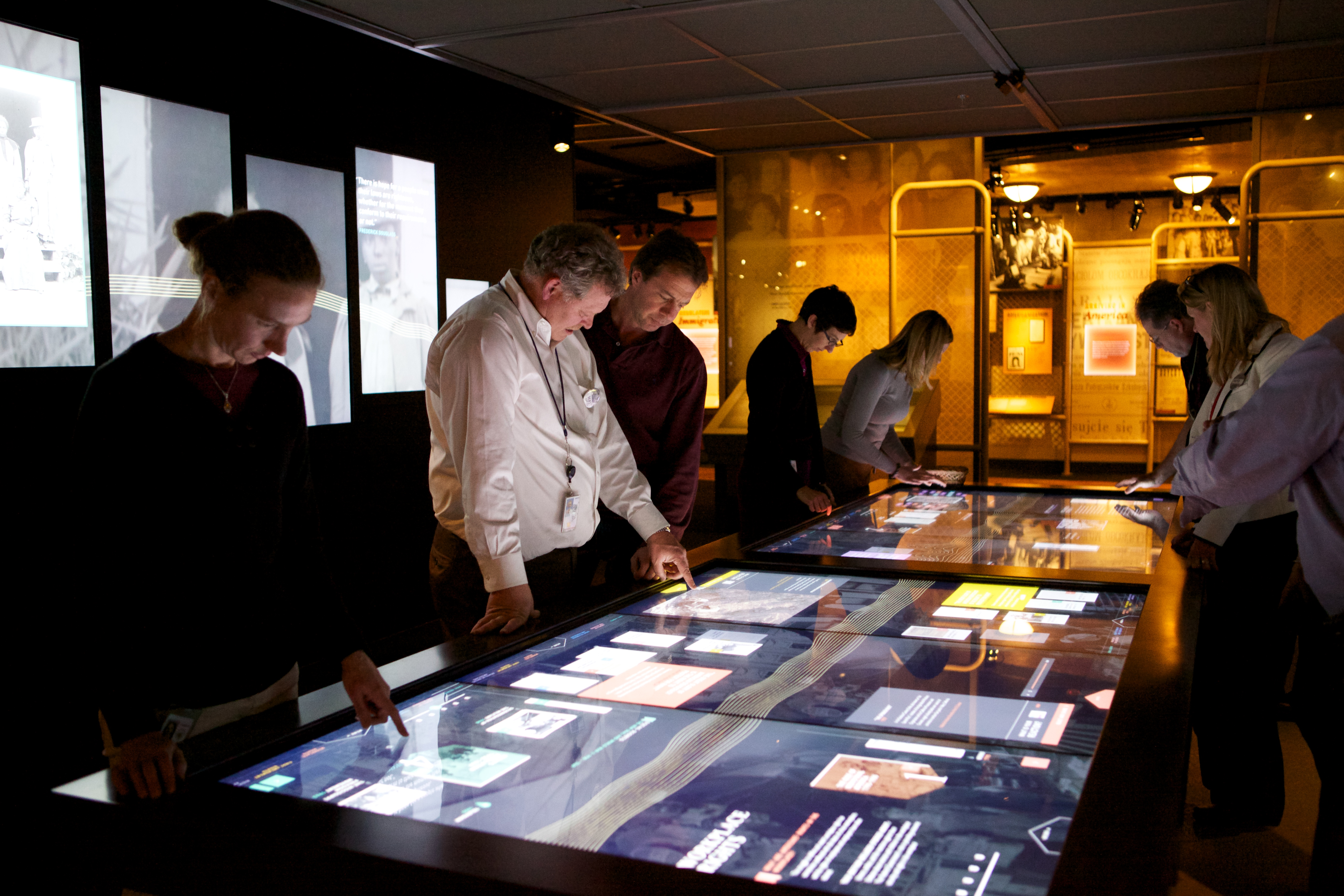 Washington, DC-area staff try out the interactive table at a staff preview of the Records of Rights exhibit in the David M. Rubenstein Gallery.