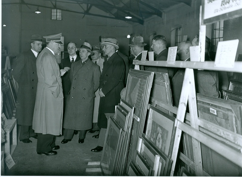Artworks that were confiscated and collected for Adolf Hitler, seen here examining art in a storage facility, were designated for a proposed Führermuseum in Linz, Austria. (National Archives, 242-HB-32016-1)