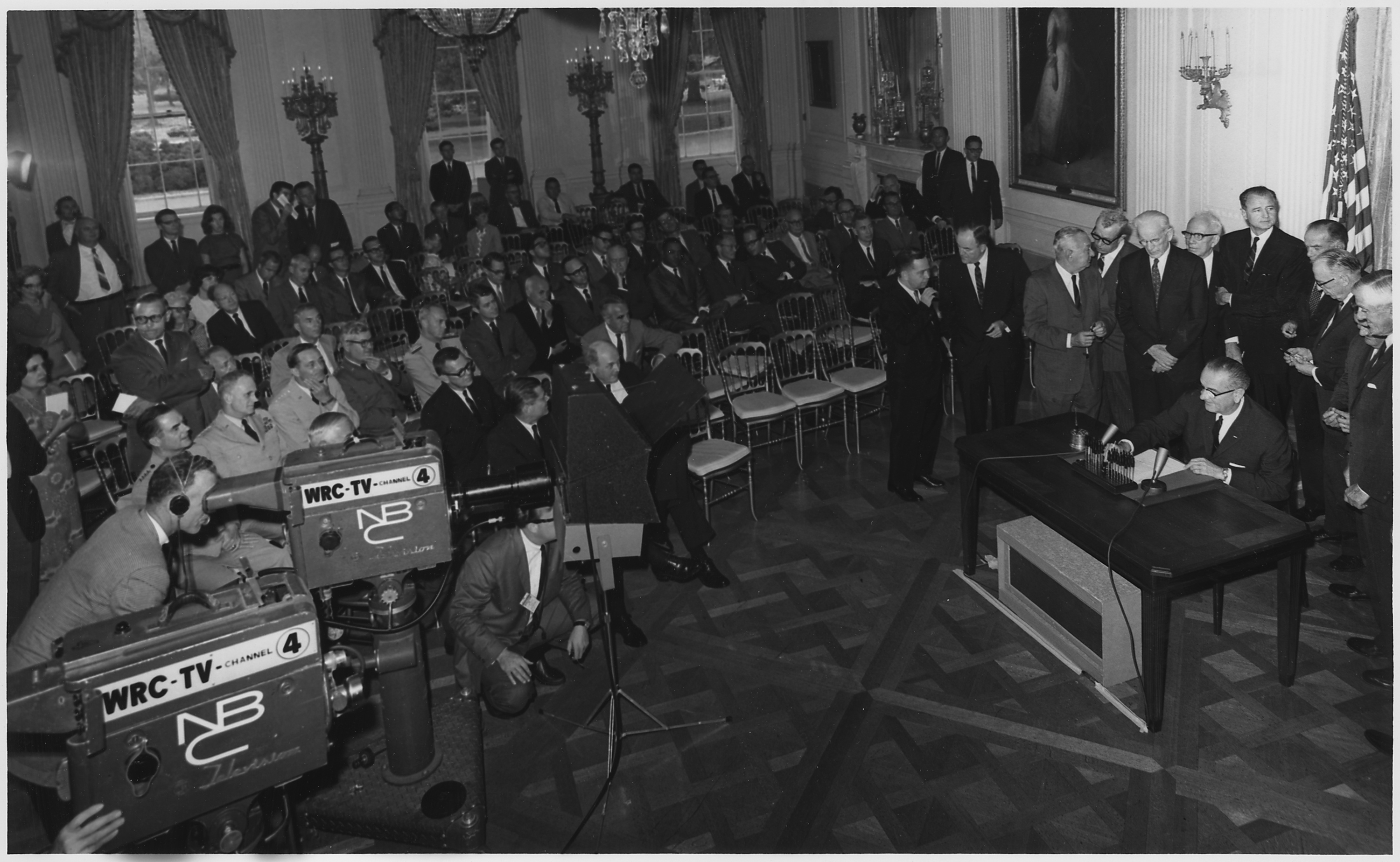 President Johnson signs the Gulf of Tonkin Resolution in the White House East Room as congressional leaders look on, August 10, 1964 (National Archives Identifier 192483)