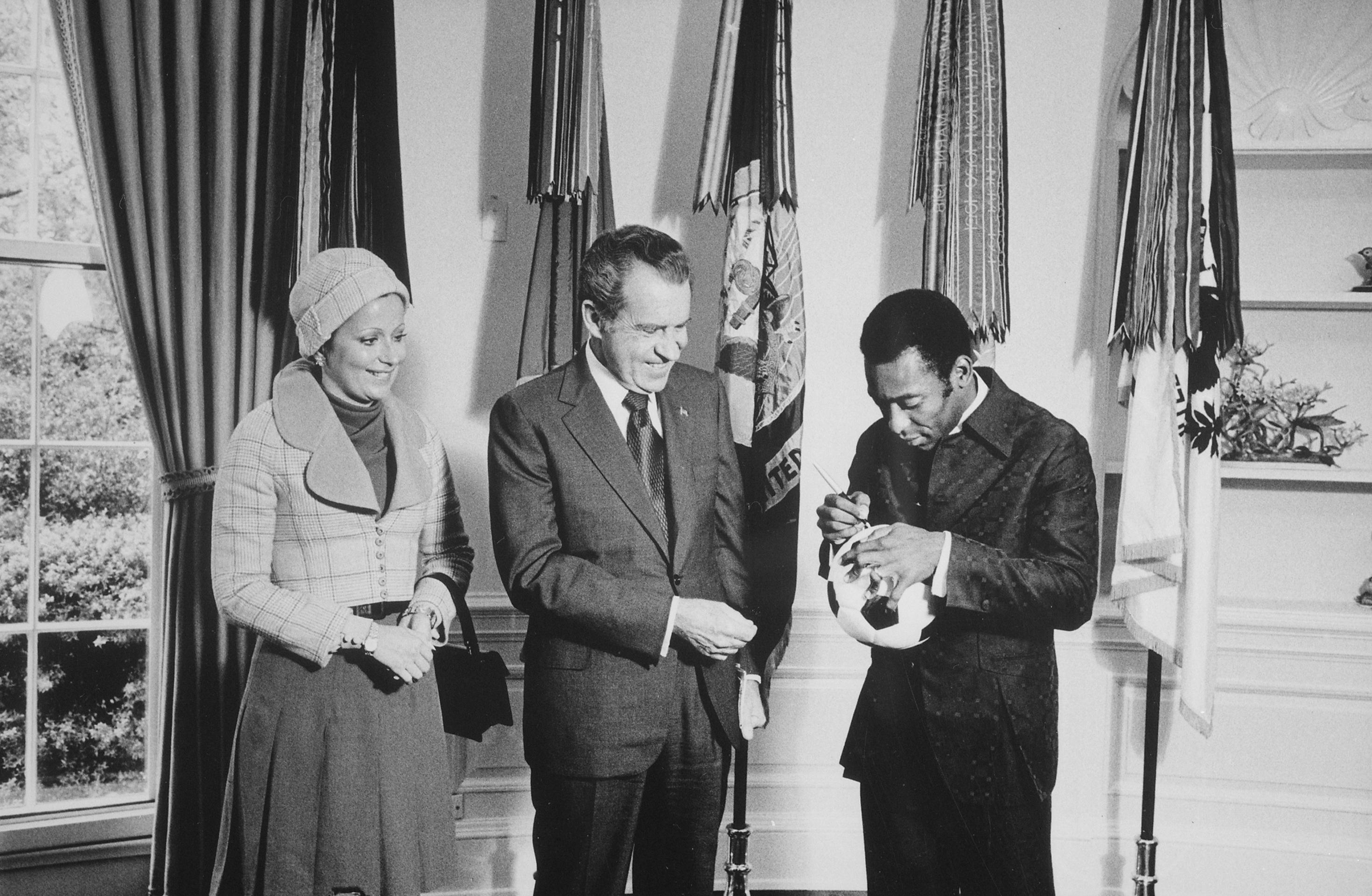 "President Nixon meeting with Edson ""Pele"" Arantes do Nascimento, retired professional Brazilian soccer player and Director of the International Soccer Program sponsored by PepsiCo. Pele autographs a soccer ball for President Nixon, 05/08/1973. (National Archives Identifier 194508)"
