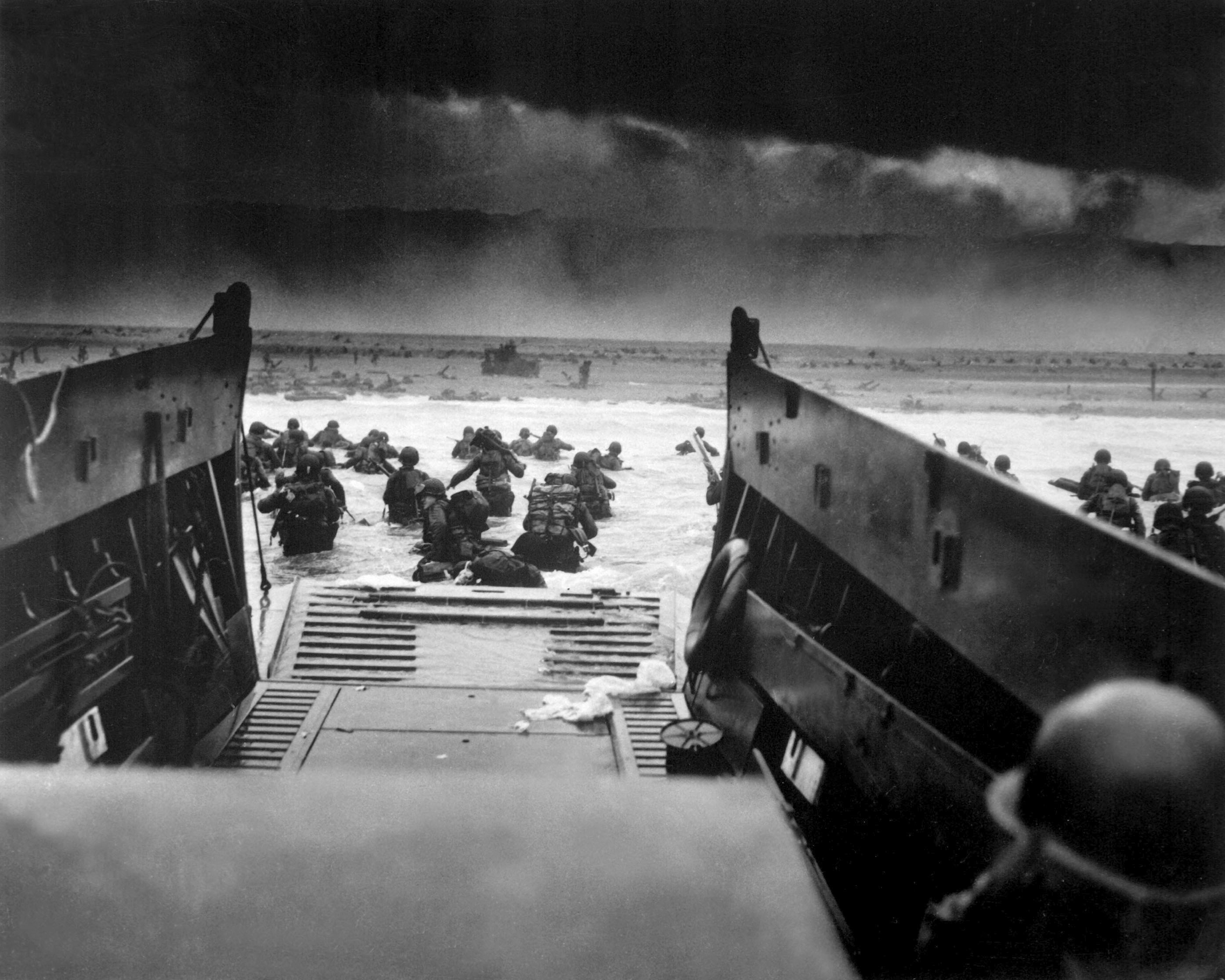 A view on June 6, 1944, from a coast Guard Barge hitting the French coast with the first waves of invaders.  U.S. troops wade ashore  under heavy machine gun fire  from Nazi beach nests.