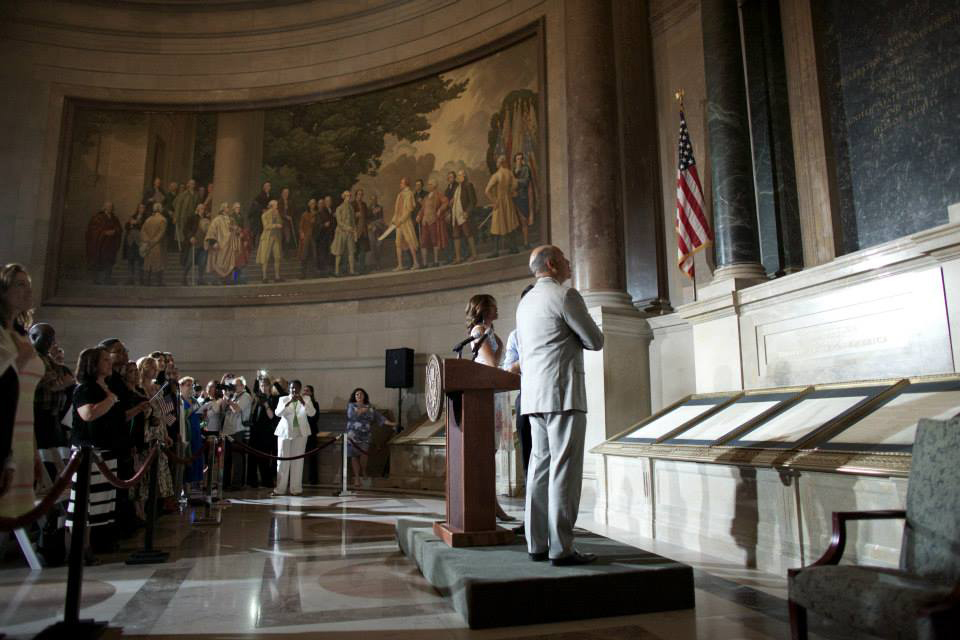 First Lady Michelle Obama, Secretary of Homeland Security Jeh Charles Johnson, and new citizen Juan Cua Monroy lead the new citizens in the Pledge of Allegiance in the National Archives, June 18, 2014. (Photo Credit: Jeff Reed, National Archives)