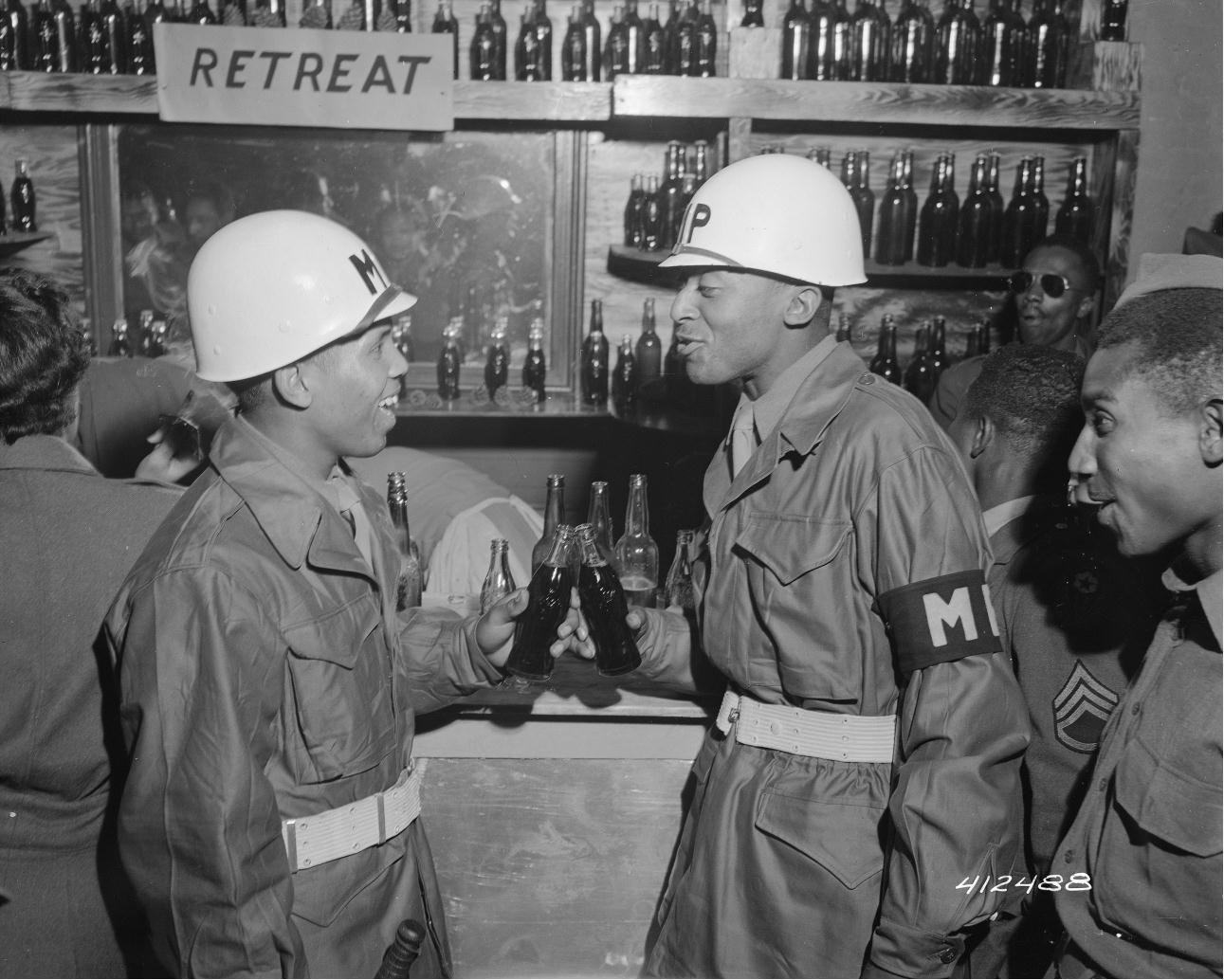 """Military Police officers toast with their Coca-Colas at a """"Retreat Club,"""" July 21, 1945. (Records of the Office of the Chief Signal Officer, National Archives)"""