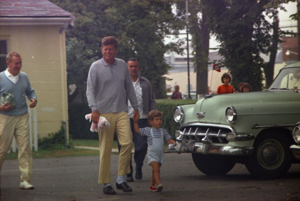 "President John F. Kennedy and John F. Kennedy, Jr., depart a candy store in Hyannis Port, Massachusetts, during Labor Day Weekend. Under Secretary of the Navy, Paul B. ""Red"" Fay, walks at left; White House Secret Service agent, Hank Rybka, walks behind President Kennedy."