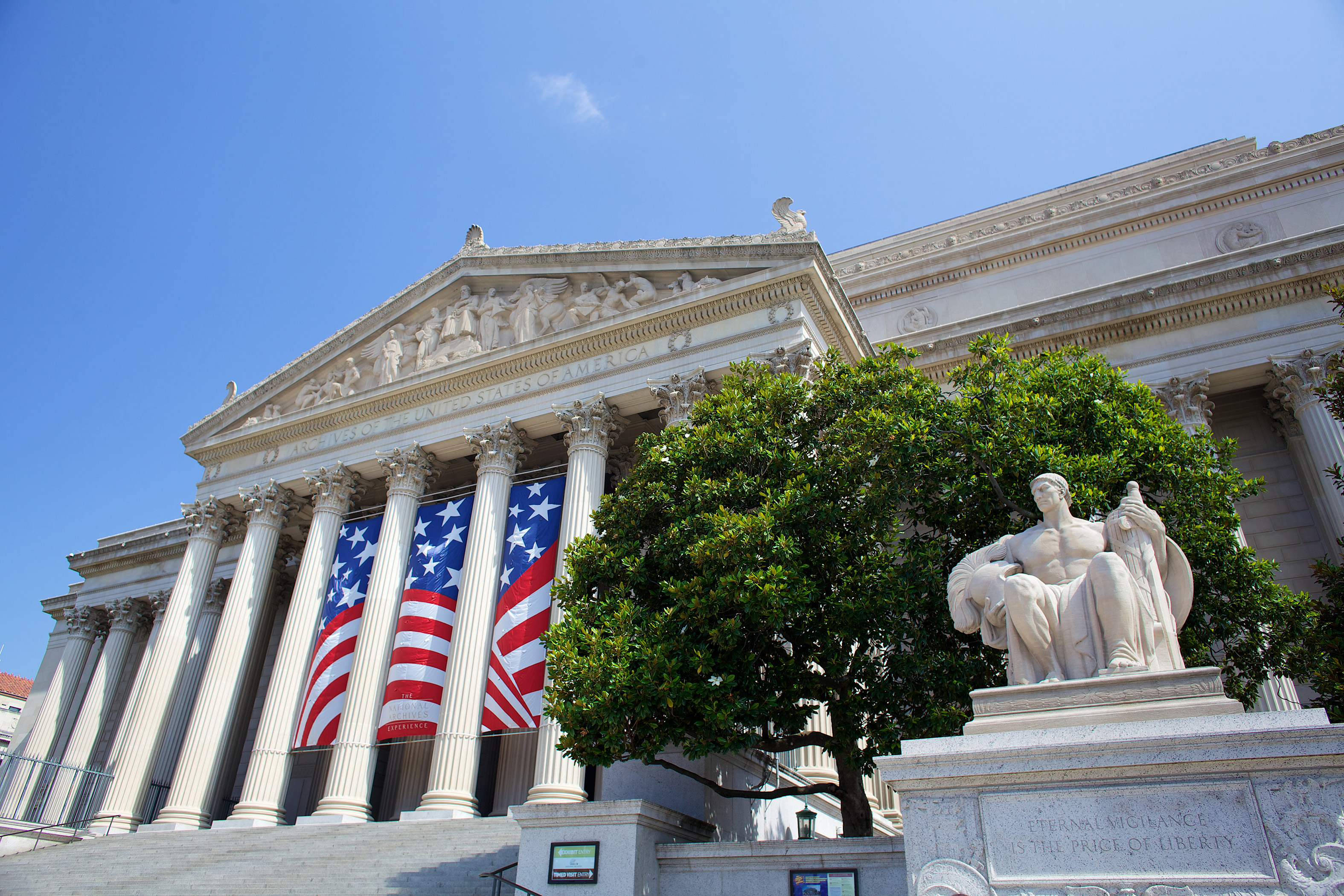 Photograph of the National Archives Building Constitution Avenue Entrance showing the annual Independence Day celebration banners (also shown is the statue Guardianship by James Earle Fraser), 2014. (Photograph by Jeff Reed, National Archives)